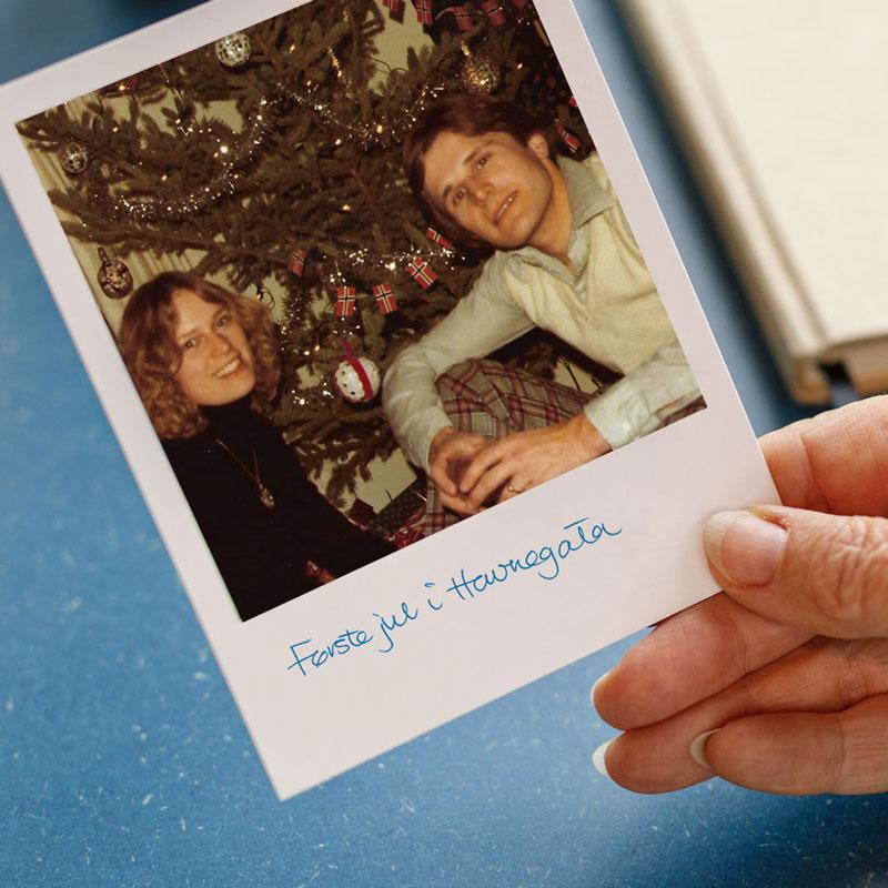 Eldre polaroidbilde av blide av 2 mennesker foran et juletre