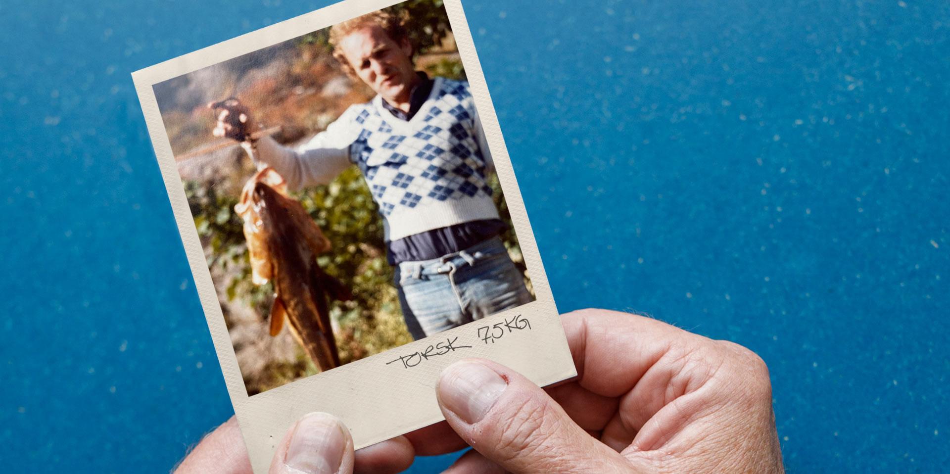 Eldre polaroidbilde av en mann som holder opp en stor fisk